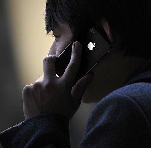 Телефон менен сүйлөшүп жаткан адам. Архив