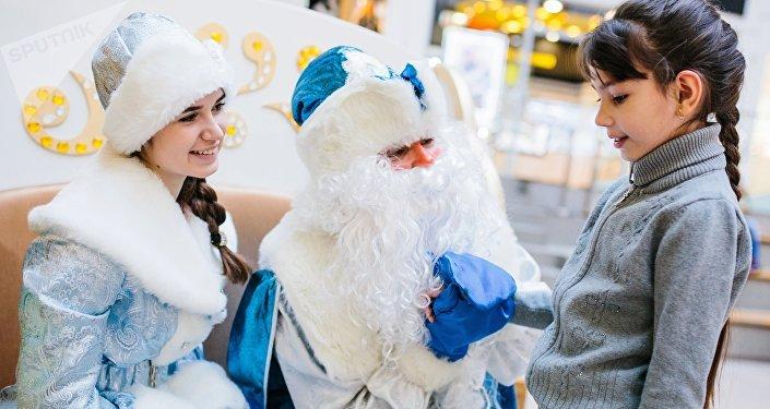 Дед Мороз и Снегурочка общаются с девочкой. Архивное фото