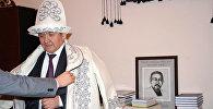 Министр культуры, информации и туризма КР Султан Жумагулов, когда ему дарят чапан (верхняя теплая одежда) и ак калпак (национальный головной убор). Архивное фото