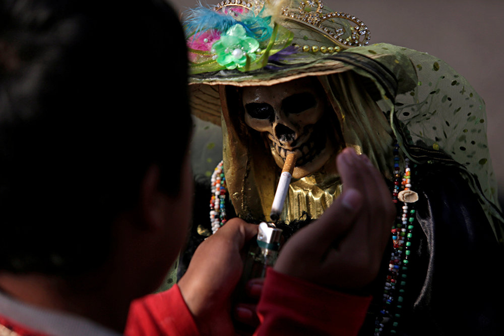 Мехико шаарында Санта-Муэртенин кебине тамеки күйүгүзүп берип жаткан адам
