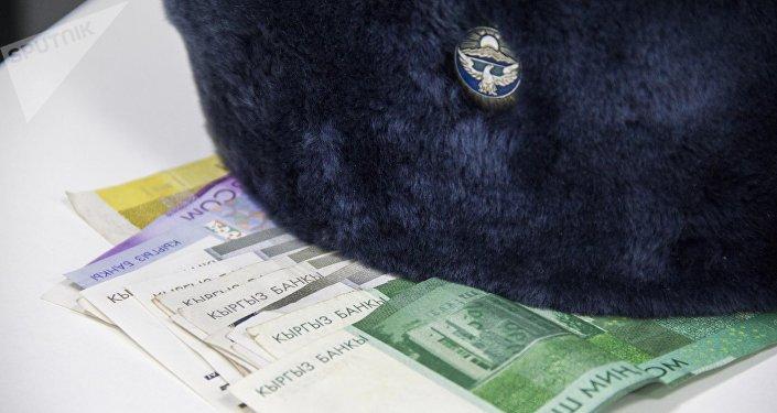 Фуражка сотрудника Министерстве Внутренних дел Кыргызстана и деньги. Архивдик сүрөт