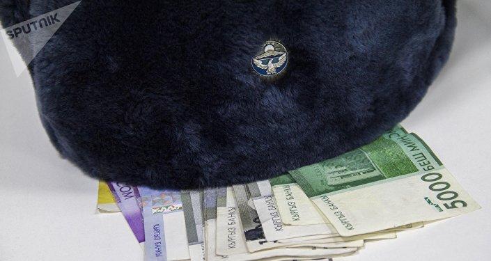 Фуражка сотрудника Министерстве Внутренних дел Кыргызстана и деньги. Архивное фото