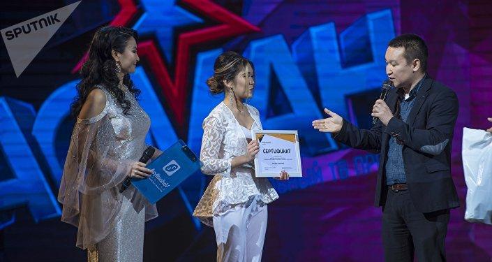 Sputnik Кыргызстан агенттигинин шеф-редактору Эркин Алымбеков Асман шоусунун катышуучусу Мэлани Сариевага сыйлык тапшыруу учурунда