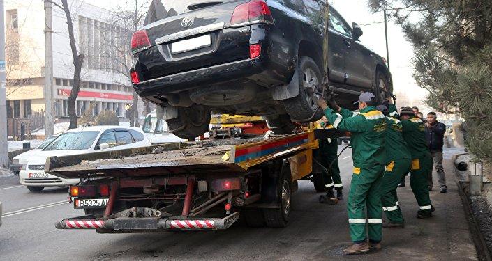 Сотрудники эвакуируют автомобиль за неправильную парковку в Бишкеке. Архивное фото