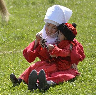 Женщина играет с ребенком во время фестиваля кочевников в ущелье Чункурчак. Архивное фото