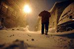 Человек гуляет по улице во время снежной бури. Архивное фото
