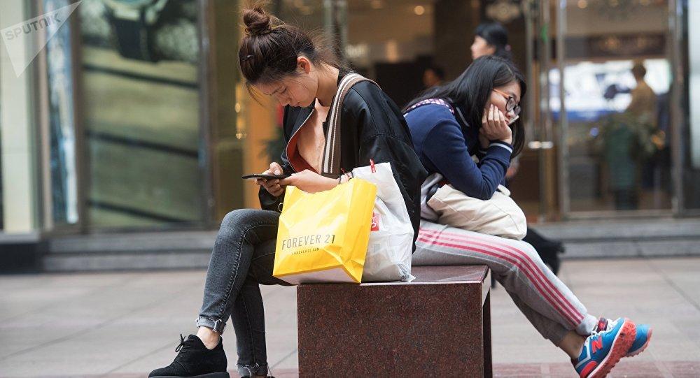 Девушка сидит с телефоном на руках. Архивное фото