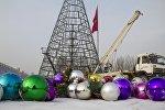 Сотрудники муниципального предприятия Тазалык демонтируют новогодние украшения на площади Ала-Тоо