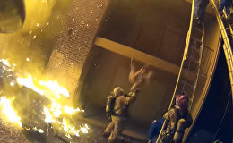 Спасатель поймал девочку, сброшенную с 3-го этажа во время пожара, — видео