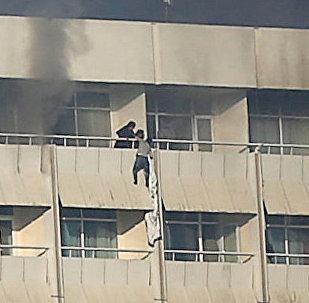 Человек пытается спуститься с балкона в Интерконтинентальном отеле во время нападения боевиков в Кабуле. Афганистан 21 января 2018 года