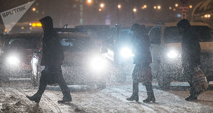 Прохожие переходят дорогу во время снегопада. Архивное фото