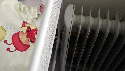 Новорожденный ребенок спит рядом с электрическим обогревателем. Архивное фото