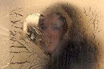 Девушка смотрит через замерзшее окно. Архивное фото