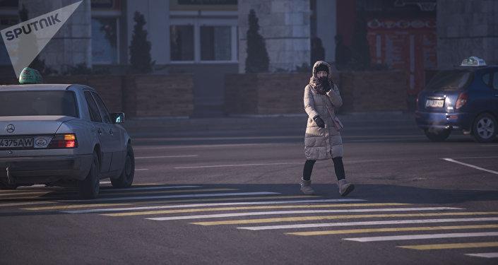Девушка переходит дорогу на одной из улиц Бишкека. Архивное фото