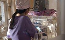Медсестра ухаживает за новорожденным ребенком в роддоме. Архивное фото