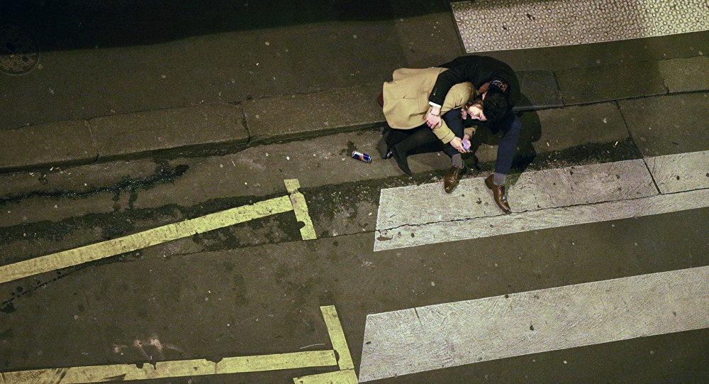Пара сидит на тротуаре на улице. Архивное фото