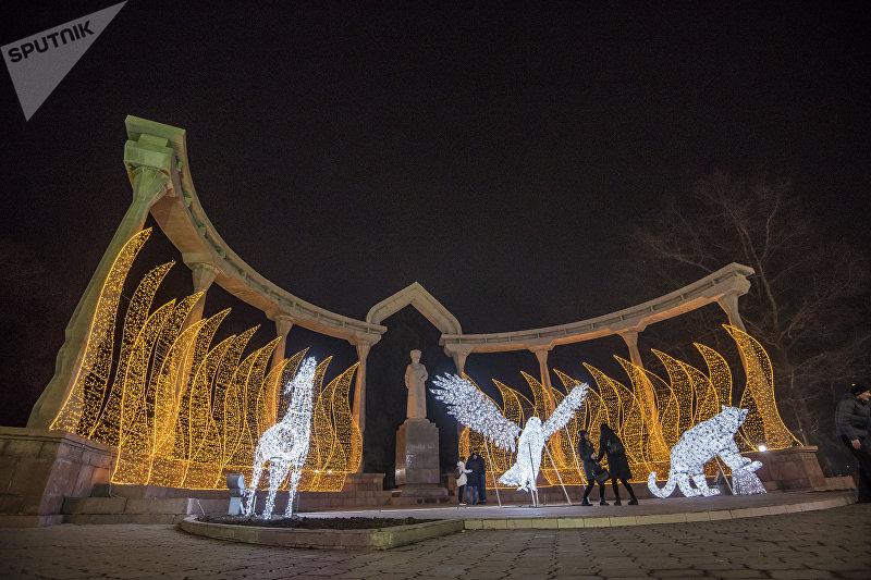 Горожане у памятника Курманжан-Датке в Бишкеке, украшенной по случаи нового года