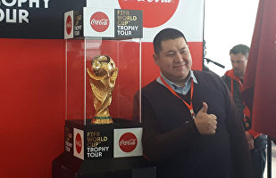 Люди фотографируются с кубком Чемпионата мира по футболу в аэропорту Манас