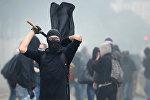 Человек в маске держит черный флаг. Архивное фото