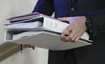 Офисный работник с документами в руке. Архивное фото