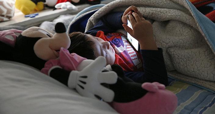 Мальчик смотрит мультфильм на сотовом телефоне лежа в постели. Архивное фото