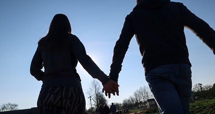 Парень и девушка гуляют по парку. Архивное фото