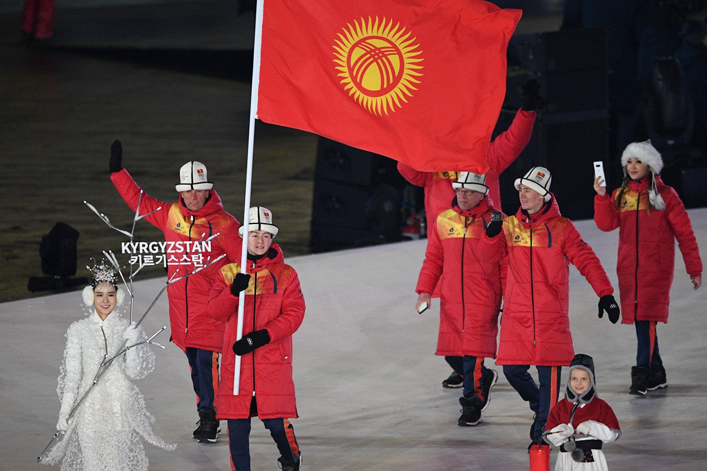 Спортсмен Тариэль Жаркымбаев несет флаг Кыргызстана в Пхенчханн, Южная Корея. 9 февраля 2018 года