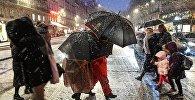 Прохожие на пешеходном переходе во время снегопада в Париже