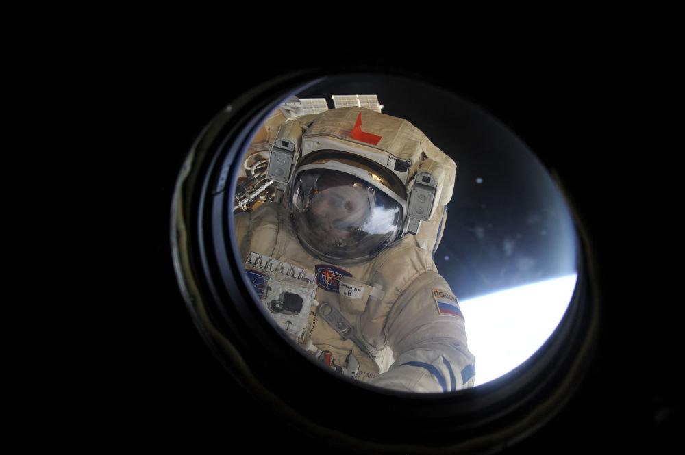Роскосмостун космонавты Михаил Корниенко кеменин терезесин тазалап жатат