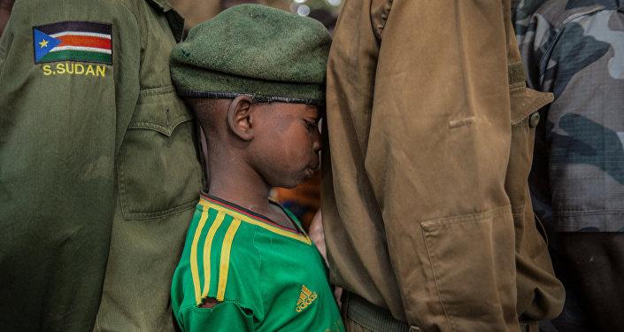 Мальчик стоит в очереди на церемонии освобождения от службы в армии в Южном Судане. Было выпущено в общей сложности более 300 детей-солдат, в том числе 87 девочек. На церемонии в Ямбио дети были официально разоружены и снабжены гражданской одеждой.