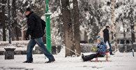 Мужчина катает ребенка на санках. Архивное фото