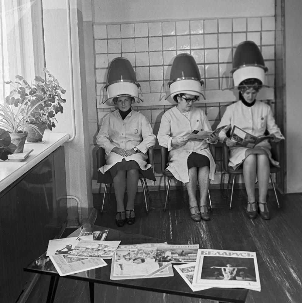 Женщины сидят в парикмахерской под сушилками для волос
