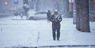Мужчина идет по улице во время снегопада. Архивное фото
