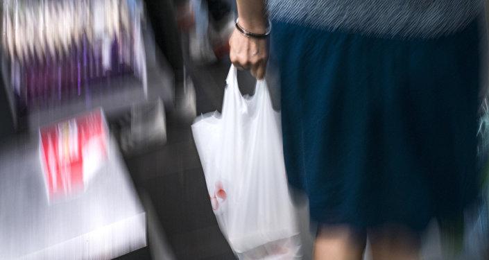 Женщина с полиэтиленовым пакетом в руке. Архивное фото