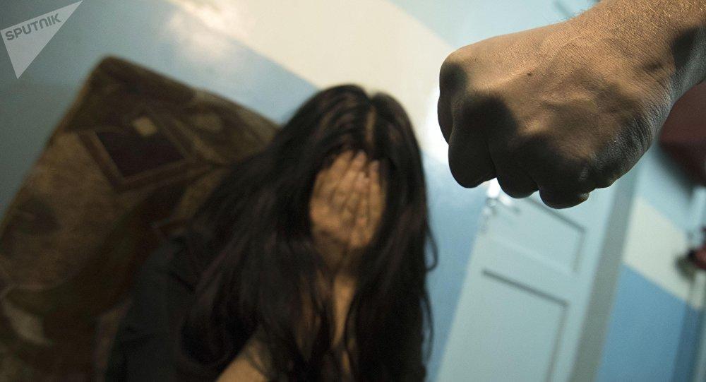 Мужской кулак на фоне плачущей женщины. Иллюстративное фото
