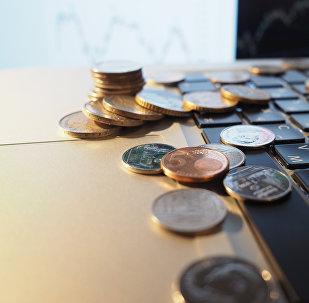 Монеты на ноутбуке. Архивное фото