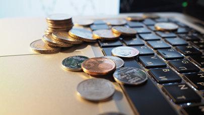 Монеты на клавиатуре ноутбука. Архивное фото