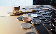 Монеты на клавиатуре ноутбуке. Архивное фото
