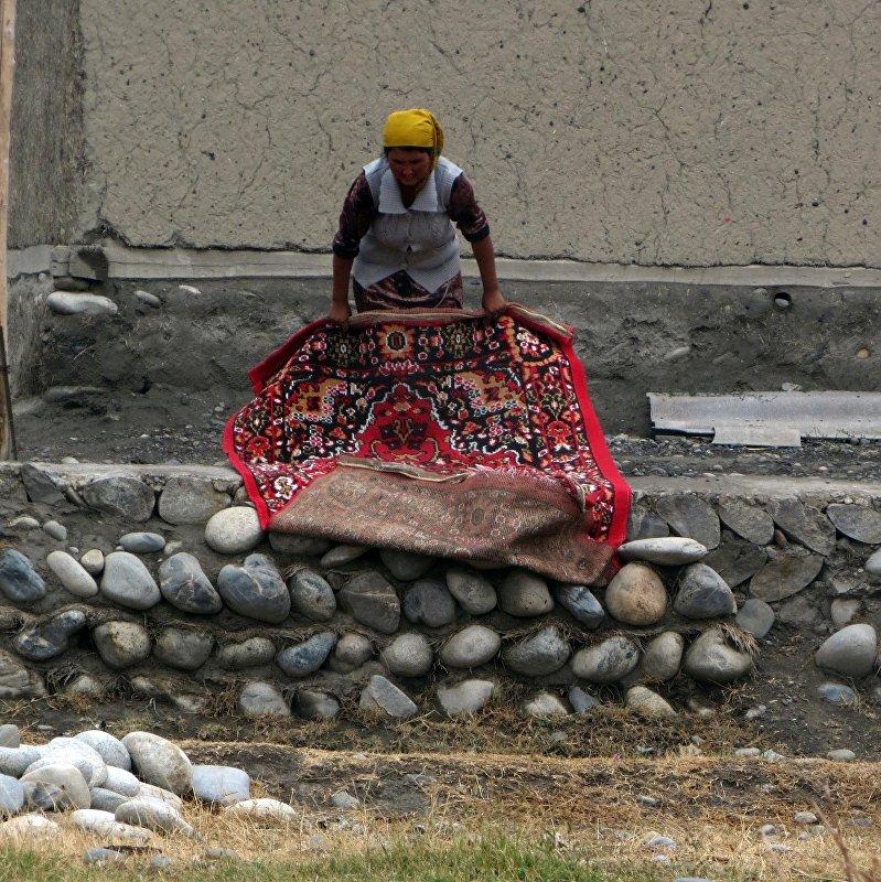 Ярко одетая женщина у домов в анклаве Чон-Гара