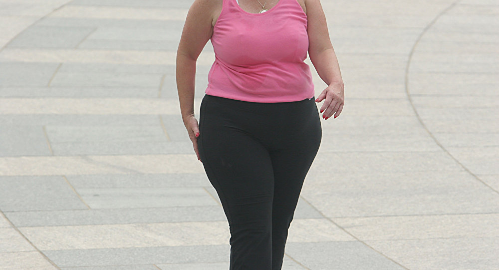 Женщин, страдающая ожирением, идет по улице. Архивное фото