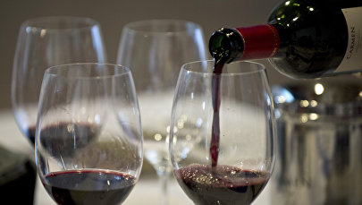 Официант разливает вино в бокал. Архивное фото