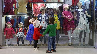 Мальчик и девочка смотрят на витрину с детской одеждой. Архивное фото