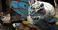 Сотрудник завода высыпает в пресс отсортированные пластиковые бутылки. Архивное фото