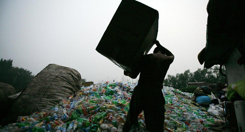Мужчина с коробкой пластиковых бутылок. Архивное фото