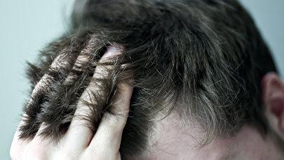 Мужчина держится за волосы. Архивное фото
