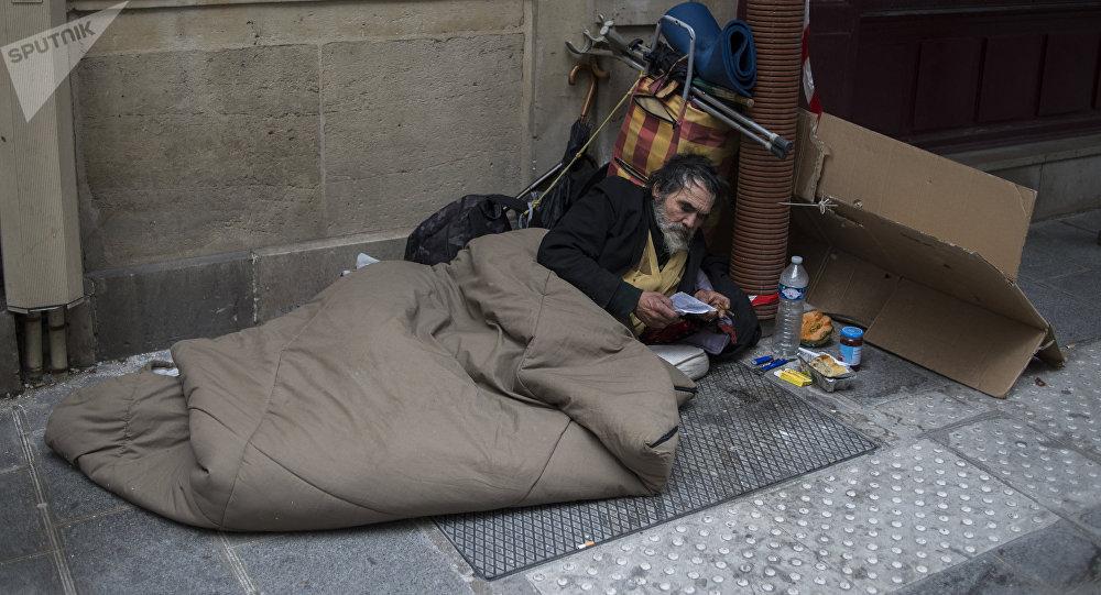 Парижский бездомный спит на одной из улиц города. Архивное фото