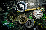 Сувенирные монеты с логотипами криптовалют Bitcoin, Litecoin и Ethereum на плате компьютера