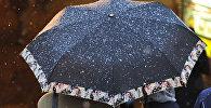 Женщина под зонтом идет по улице. Архивное фото