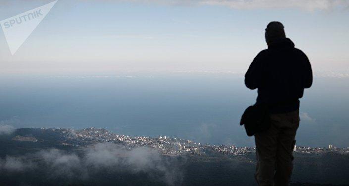 Отдыхающий смотрит на город с горы. Архивное фото