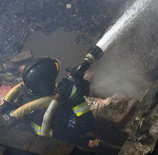Сотрудник пожарной службы тушит пожар. Архивное фото